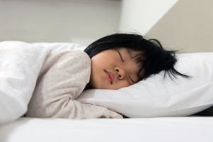 Young girl sleeping on bed with white sheets