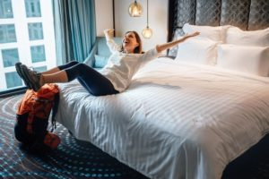 Woman traveling with sleep apnea, relaxing on hotel bed