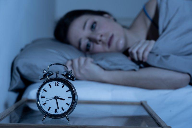 Woman with sleep apnea and anxiety awake in bed