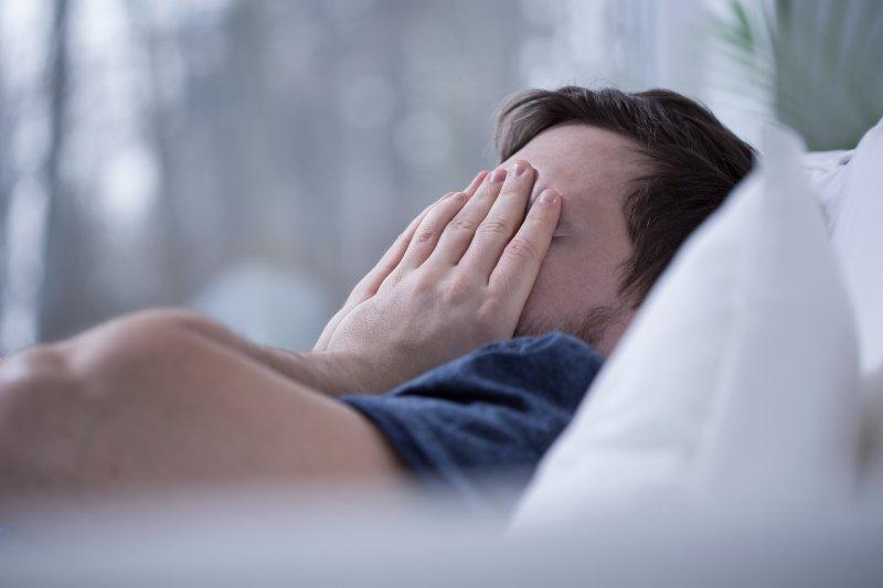 Man with sleep apnea lying awake in bed